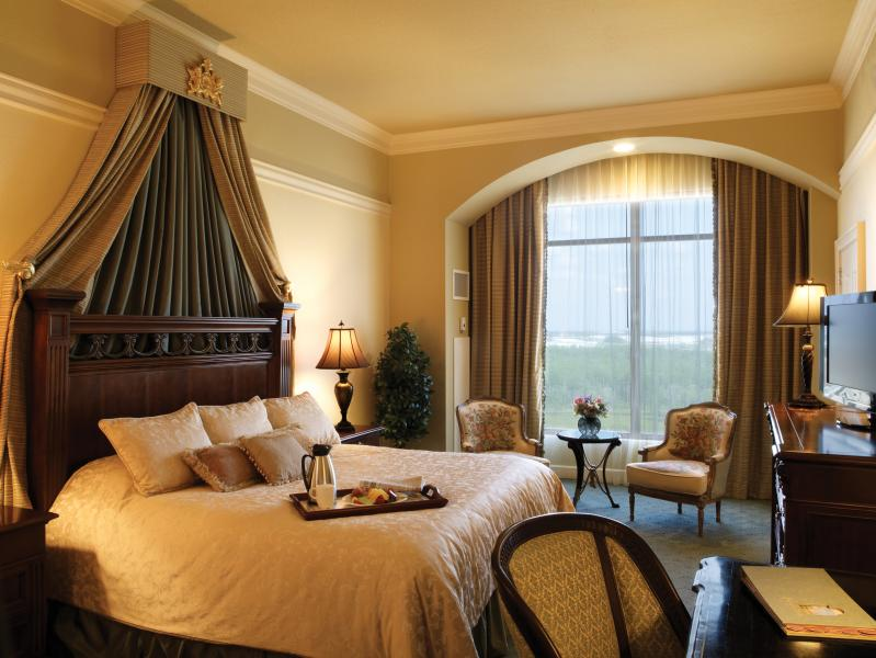 A regal Presidential Suite guestroom features plush bedding and opulent decor.