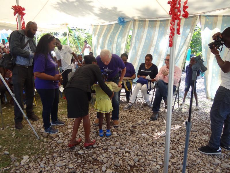 Dec. 2017 (Haiti) Harris Rosen thanks a young Haitian girl for her present of an official Haiti straw hat.
