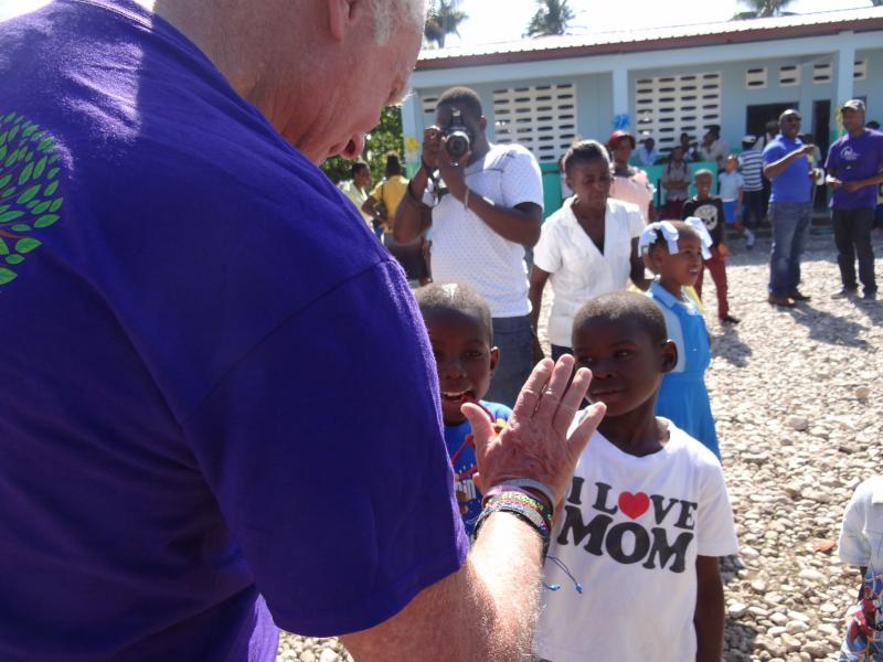 Dec. 2017 (Haiti) Harris Rosen shares a high five with a student at the dedication of the new school.