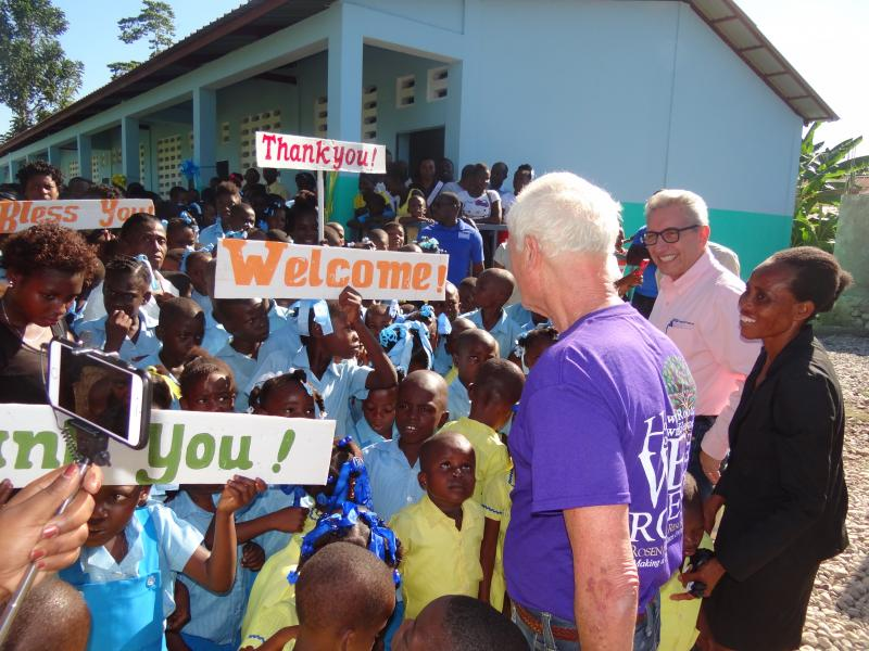 Dec. 2017 (Haiti) Harris Rosen receives a warm welcome from Haitian schoolchildren at the dedication of their new school.