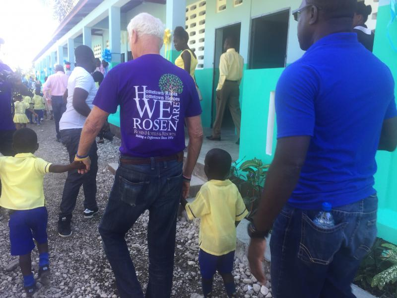 Dec. 2017 (Haiti) Harris Rosen gets a helping hand from schoolchildren excited about their school's dedication.