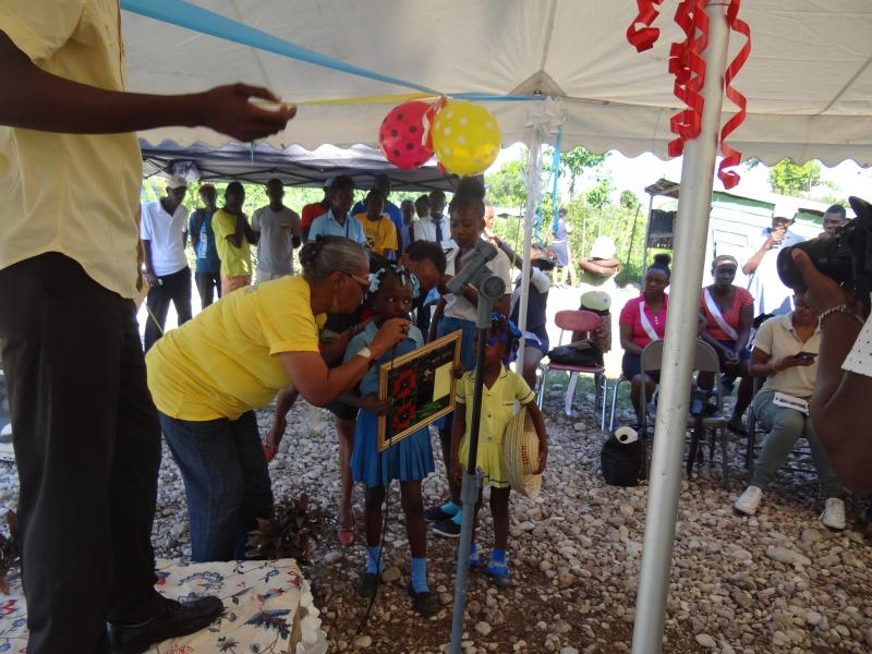 Dec. 2017 (Haiti) Schoolchildren present thank you gifts to Harris Rosen as their school's dedication ceremony.