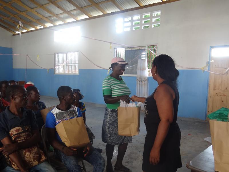 Dec. 2017 (Haiti) Grateful homeowners receive gifs for their new homes built by Harris Rosen.