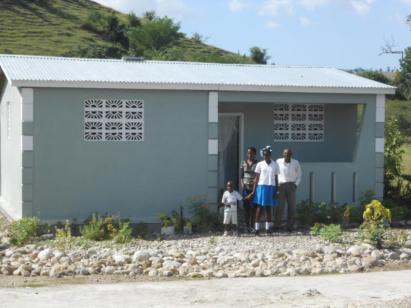 Dec. 2017 (Haiti) A family poses in front of their new home, rebuilt by Harris Rosen after the 2016 hurricane.
